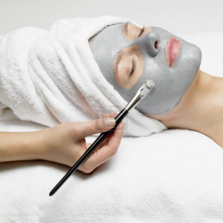 Application of a cosmetic mask on the face of young woman at the beautician