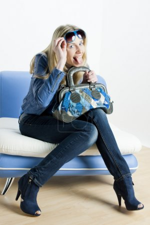 Woman wearing blue clothes with handbag sitting on sofa