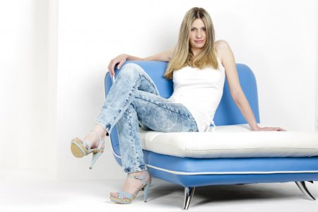 Woman sitting on sofa wearing jeans and summer sho...