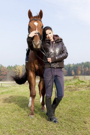 equestrian with her horse on meadow