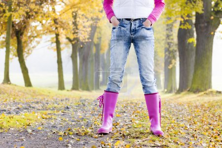 detail of woman wearing rubber boots in autumnal alley