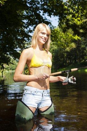 woman fishing in Jizera river, Czech Republic