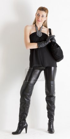 standing woman wearing black clothes with a handbag