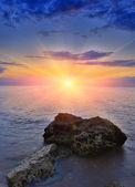 stones on sea against sunset