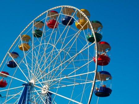 Ferris wheel in the park against blue sky...