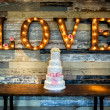 Image of a wedding cake with the word love as sina...