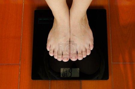 Photo pour Une fille debout sur la machine à peser pour savoir quel poids elle a. cela fait partie du plan d'ajustement . - image libre de droit