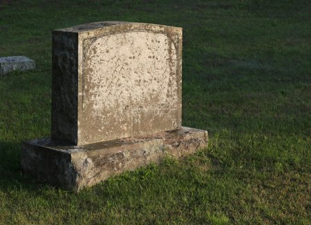 A large gravestone in a graveyard, shot in the gol...