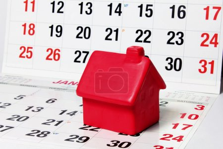 Photo for Close Up of Miniature House on Calendar Pages - Royalty Free Image