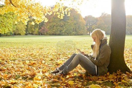 Photo pour Jeune femme avec tablette numérique dans le parc d'automne - image libre de droit