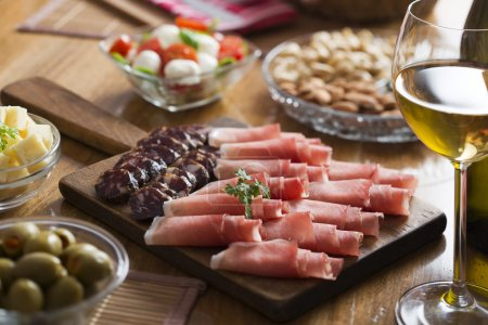 Full table of prosciutto, olives, cheese, salad an...