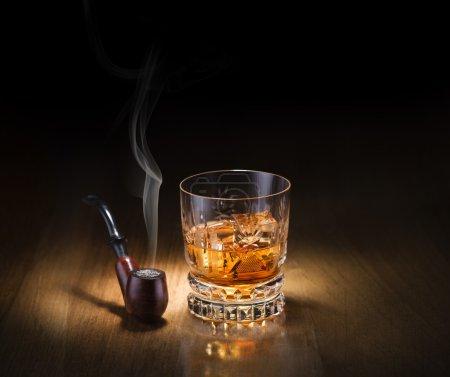 Photo pour Whisky et pipe à fumer sur fond en bois - image libre de droit