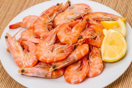 Photo pour Crevettes cuites avec du citron sur une plaque blanche - image libre de droit
