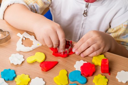 Photo for Hands of a Child make figurines of modeling clay - Royalty Free Image