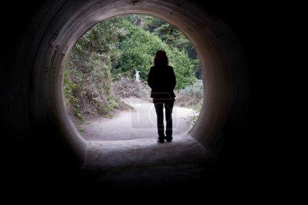 Photo pour Une femme passe d'un tunnel sombre à la lumière du jour - image libre de droit