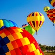 Hot air balloons brighten the blue morning sky in ...