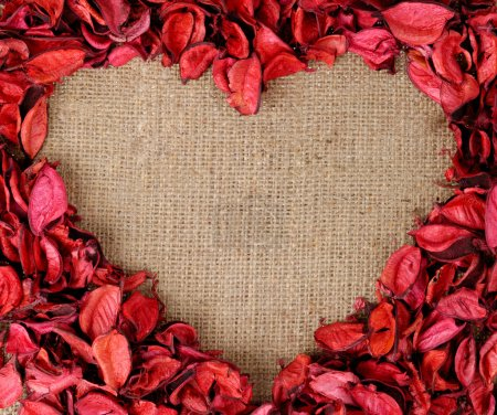 Photo for Heart-shaped frame made from red flower petals on burlap fabric background - Royalty Free Image