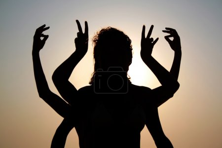 Girls silhouettes with arms raised up outdoor