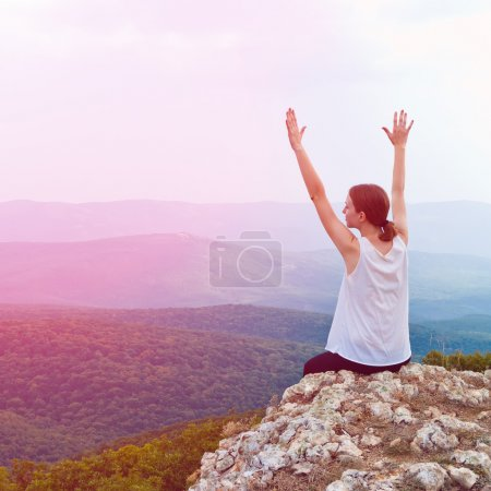 Happy young girl sitting on a cliff side