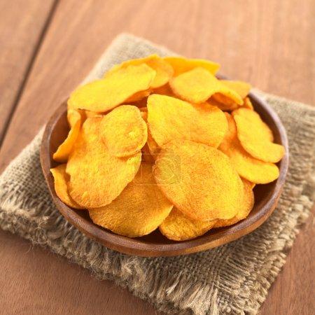 Crispy Peruvian sweet potato chips on wooden plate...