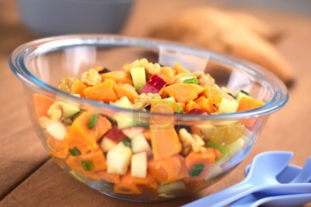 Photo for Glass bowl of fresh salad made of cooked sweet potatoes, fresh apples, nuts, raisins and shallots (Selective Focus, Focus one third into the salad) - Royalty Free Image