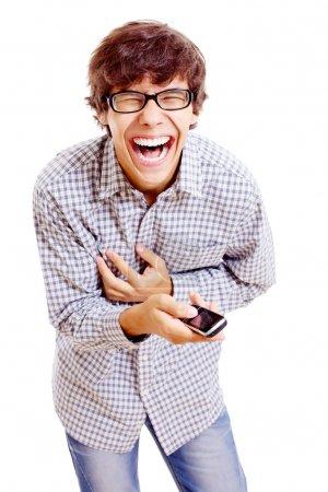 Photo pour Jeune homme latin en lunettes noires et téléphone portable dans sa main doublant de rire. Isolé sur fond blanc, masque inclus - image libre de droit
