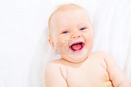 Cute pleased kid on towel