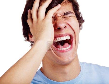 Photo pour Jeune homme avec la main sur le visage riant à haute voix isolé sur fond blanc - image libre de droit