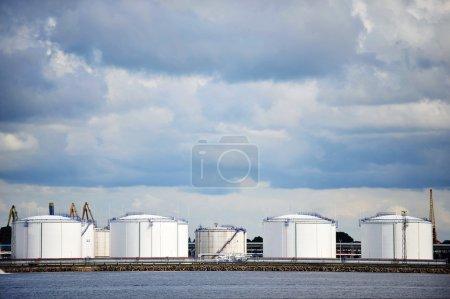 Photo pour Réservoirs de stockage de pétrole au port sous un ciel nuageux - image libre de droit