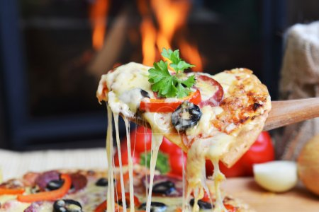 Photo for Lifting slice of pizza with pepperoni and olives - Royalty Free Image