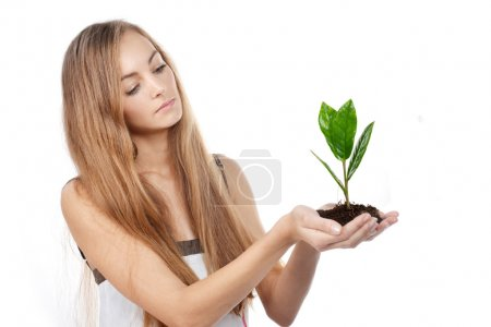 Photo for Beautiful young woman with green sprout of tree in her palms - Royalty Free Image
