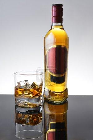 Photo pour Composition simple de verre et bouteille de whisky . - image libre de droit