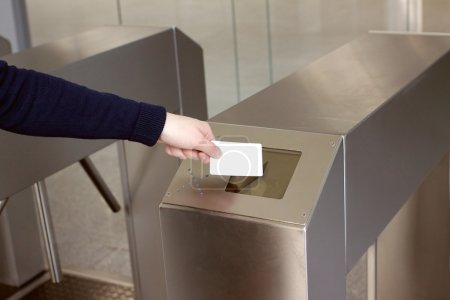 Woman's hand puts white plastic card to reader acc...