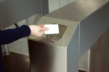 Woman's hand puts white plastic card to reader closeup