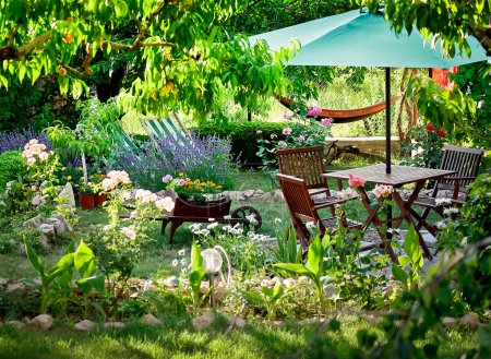 Photo for Wooden table and chairs in a beautiful garden. Landscape design of country houses. Chairs and place under an umbrella in the garden under the trees in flower beds - Royalty Free Image