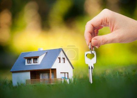 Photo pour Main tenant la clé sur fond de maison - image libre de droit