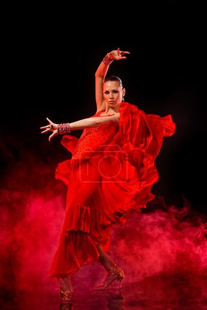 Photo for Young woman dancing Latino on dark smoky background. - Royalty Free Image