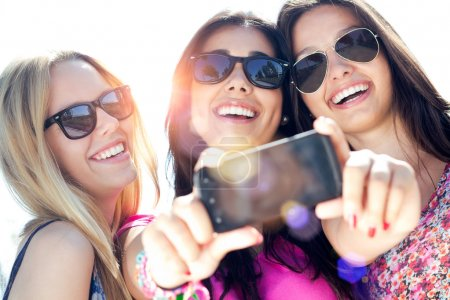 Photo for Outdoor portrait of three friends taking photos with a smartphone - Royalty Free Image