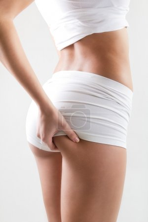 Attractive woman with perfect body checking cellulite on her but