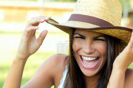 Outdoor portrait of a beautiful woman with hat