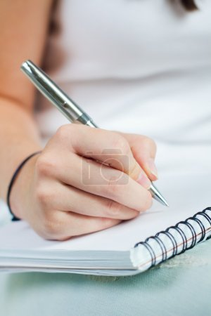 hand of young woman taking notes