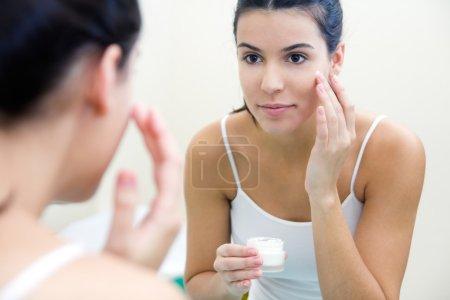 Body care. Woman applying cream on face