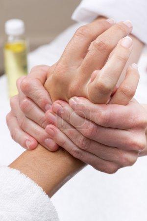 Woman enjoying hand massage at beauty spa