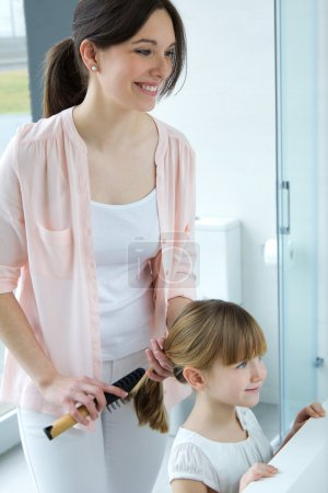 mother combing her daughter in the bathroom