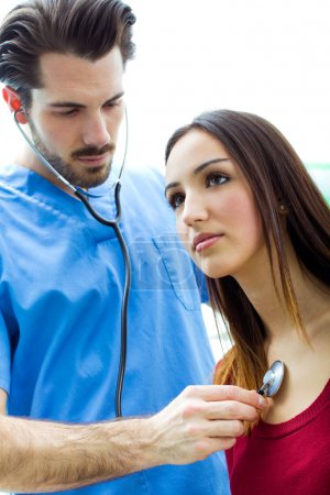 doctor with stethoscope checking a patient