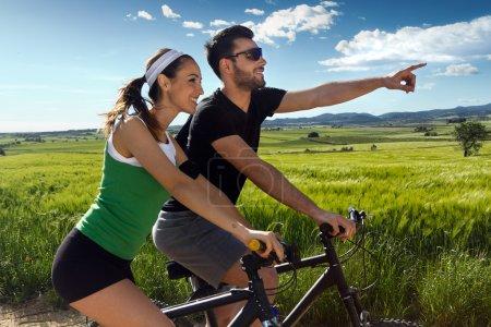 Photo pour Portrait printanier d'un jeune couple heureux en balade à vélo à la campagne - image libre de droit