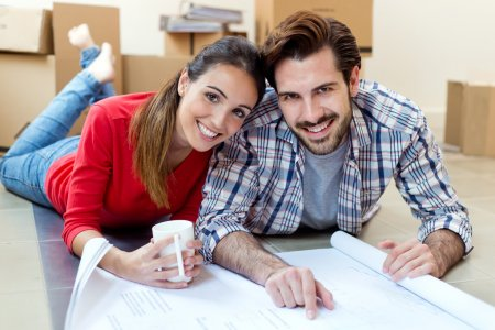 Young couple looking at the blueprints of their new home