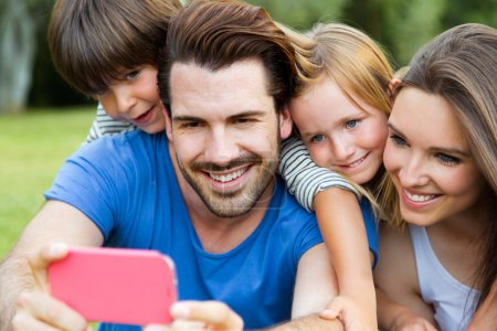 Happy young family taking selfies with her smartphone in the par