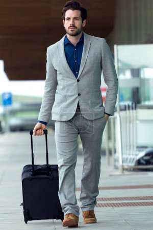 Urban business man with a suitcase walking outside in airport