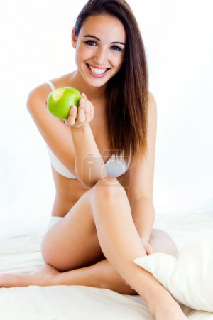 Young girl eating apple on the bed. Isolated on white.
